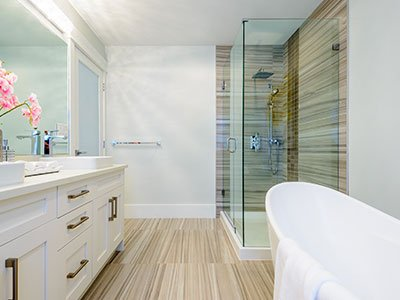 Average bathroom with light gray walls, brown striped tiles on the floor and shower wall, white cabinets, white bathtub, and large mirror.