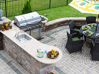 Outdoor living space with paved deck, grill and open space kitchen area with stone countertops, black round table and chairs, and a shade umbrella.
