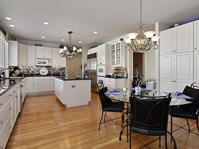 Large kitchen with white cabinets, round glass table, black chairs, wooden floor, and two chandeliers.