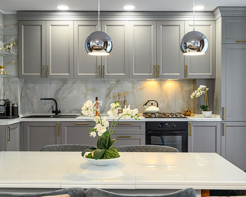 Large luxury kitchen with gray cabients and overhang lighting and whit emarble countertops