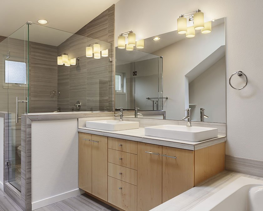 Master bathroom with wooden cabinet, double sink, large mirror, and large shower with glass walls.