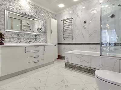 Master bathroom with white marble floor and white stone decor on the walls, white cabinets, white bathtub with glass wall, and large mirror.