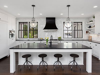 Modern kitchen with white cabinets, large island with black countertop, four black chairs, modern lighting, and dark wooden floor.