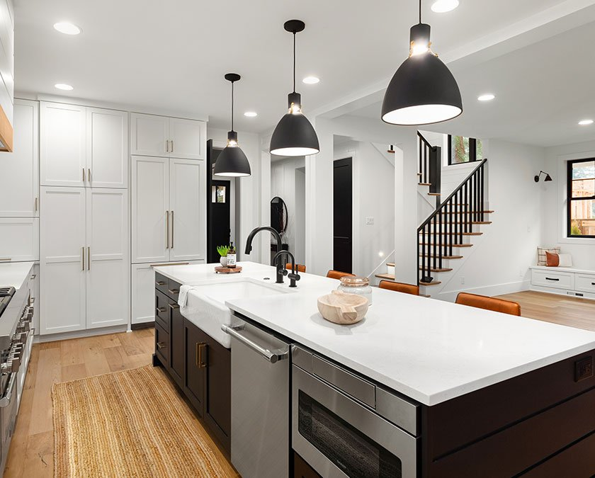 Modern kitchen with white cabinets, large dark island with white countertop, modern lighting, and wooden floor.