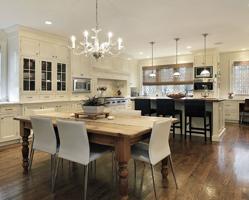 Modern kitchen with white cabinets, wooden table, white chairs, elegant chandelier, and wooden floor.