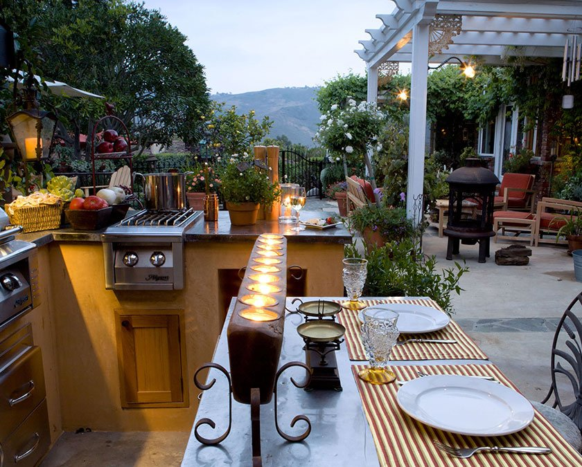 Outdoor living space with open space kitchen, grill and dining area, paved floor, and covered patio.