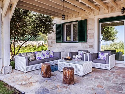 Outdoor living space with white rattan couch and table, gray seating pillows, paved floor, and wooden cover.