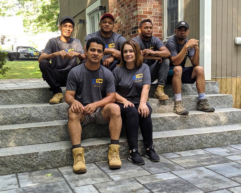 Owner posing with the team on stone paved stairs steps.